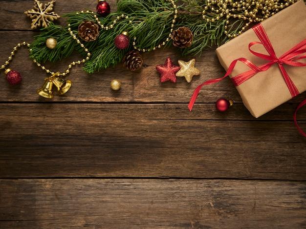 Confezione regalo di natale con rami di abete e decorazioni su fondo di legno scuro rustico