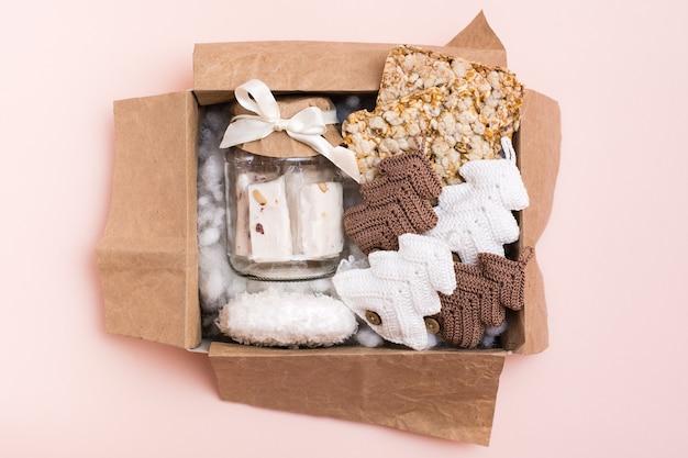 Un regalo di natale. una scatola con un barattolo di pasta, patatine di cereali e abeti lavorati a maglia. arredamento artigianale. zero sprechi