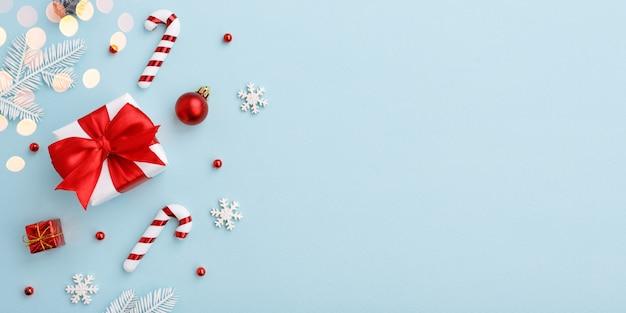 Confezione regalo di natale con fiocco rosso e decorazioni su sfondo blu pastello