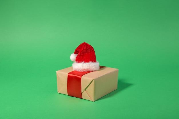 Contenitore di regalo di natale con il cappello rosso della santa su un verde con lo spazio della copia, vendita di natale, concetto festivo