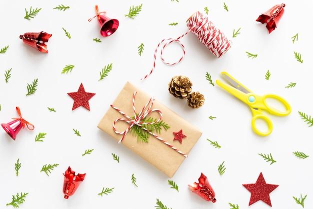 Contenitore di regalo di natale con stella rossa e pigne su sfondo bianco.