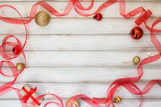 Confezione regalo di natale con fiocco in nastro e palla giocattolo su fondo di legno bianco