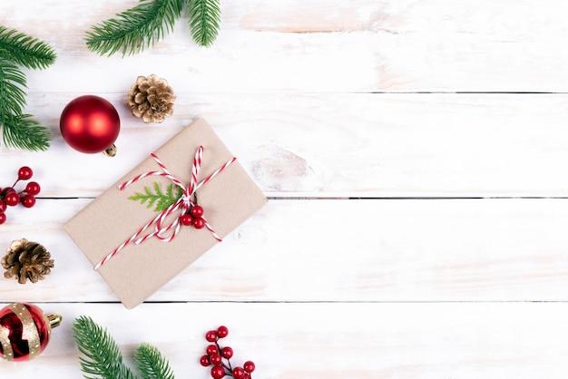 Contenitore di regalo di natale con rami di abete rosso e decorazione su fondo di legno.