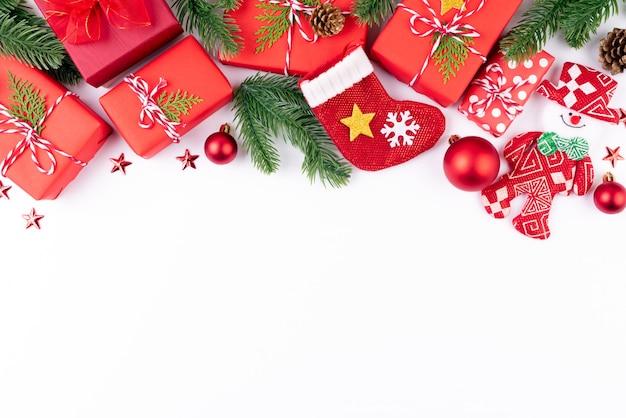 Contenitore di regalo di natale con rami di abete rosso, pigne, bacche rosse su sfondo bianco.