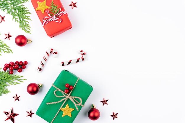 Contenitore di regalo di natale con rami di abete rosso, pigne su sfondo bianco.