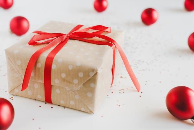 Confezione regalo di natale avvolta in carta kraft a pois, palle di natale rosse e piccoli glitter su sfondo bianco