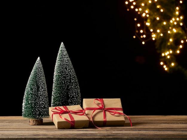 Scatole regalo di natale e albero di abete sulla tavola di legno contro luci festive sfocate, spazio per il testo