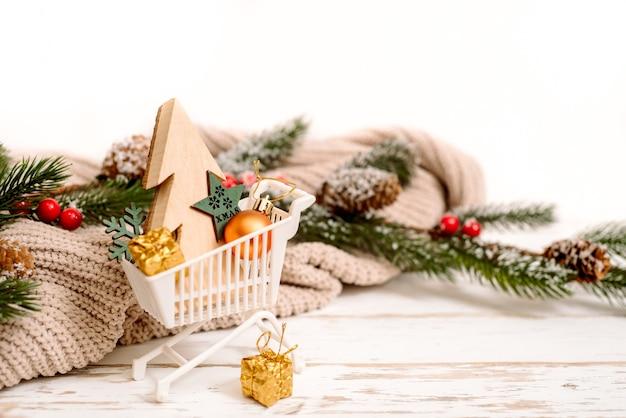 Scatole regalo di natale in un carrello con fiocchi di neve decorativi intorno, concetto di vendita di natale. accogliente maglione lavorato a maglia.