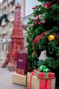 Scatole regalo di natale e pacchetti per la spesa sotto l'albero di natale si trovano su un tappeto bianco