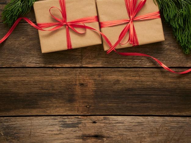 Scatole regalo di natale con rami di abete e decorazioni su fondo di legno scuro rustico