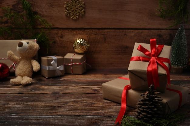 Scatole regalo di natale con nastro rosso, orsacchiotto, pigne e rami di abete sul tavolo di legno.