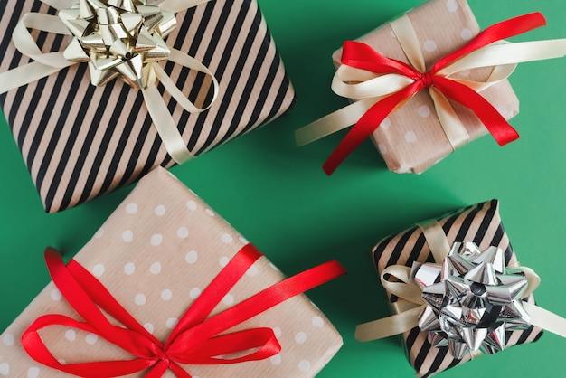 Scatole regalo di natale avvolte in carta artigianale con nastri rossi e gialli su sfondo verde