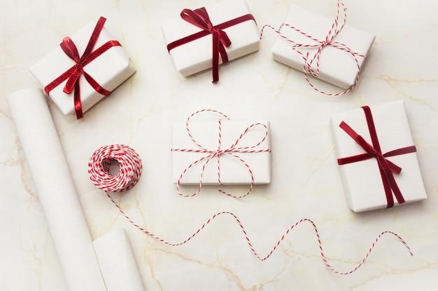 Scatole regalo di natale avvolte in carta bianca artigianale e nastro rosso decorativo.