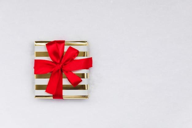 Un regalo di natale in un pacchetto festivo sulla neve, piatto laici