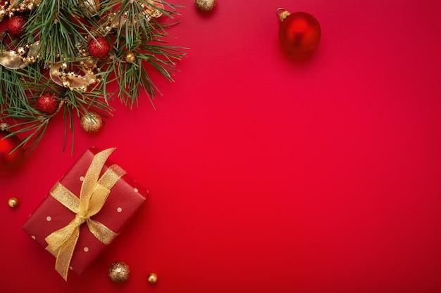 Regalo di natale e abete con decorazioni in oro su sfondo rosso.