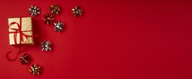 Regalo di natale in carta oro con nastro rosso