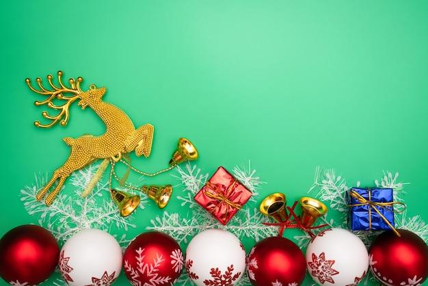 Regalo di natale, renna oro e campana su sfondo verde. vista piana, vista dall'alto