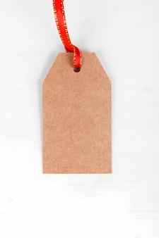 Etichetta regalo di natale di etichetta presente di carta artigianale con nastro rosso su sfondo bianco.