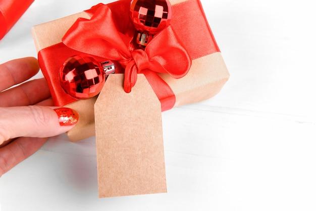 Etichetta regalo di natale con confezione regalo avvolta in carta riciclata artigianale con fiocco in nastro rosso su sfondo bianco.