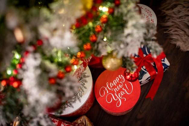 Regalo di natale sotto l'albero, la scritta sulla scatola, felice anno nuovo. umore festoso, in attesa di un miracolo