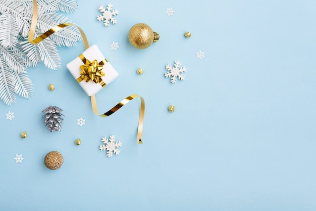 Regalo di natale con fiocco in oro e decorazioni su superficie blu