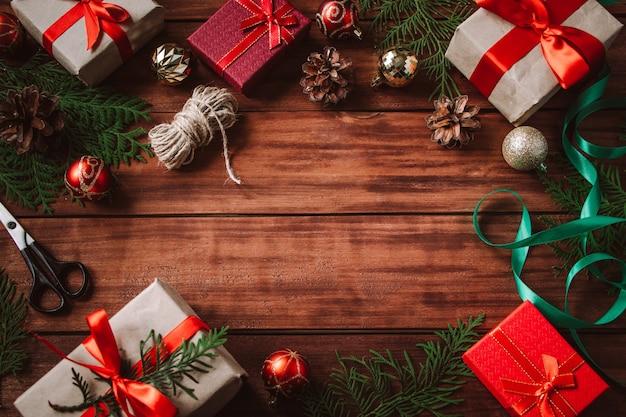 Processo di confezione regalo di natale. la donna decora la scatola con un nastro rosso.