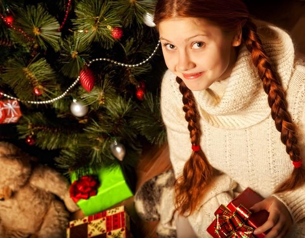 Giovane donna del regalo di natale vicino all'albero