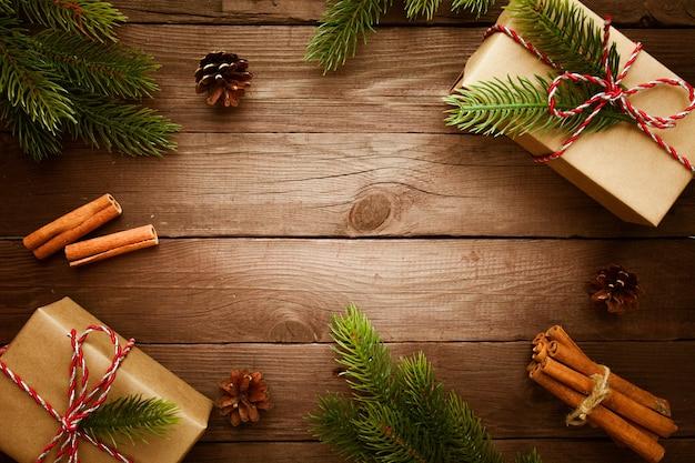 Scatole di regali di natale con rami di abete su una superficie di legno