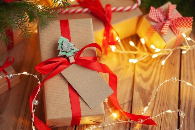 Regali di natale in confezioni artigianali su un tavolo di legno sullo sfondo di un albero di natale decorato. scatole regalo fatte a mano. vacanze di natale accogliente, concetto di umore.