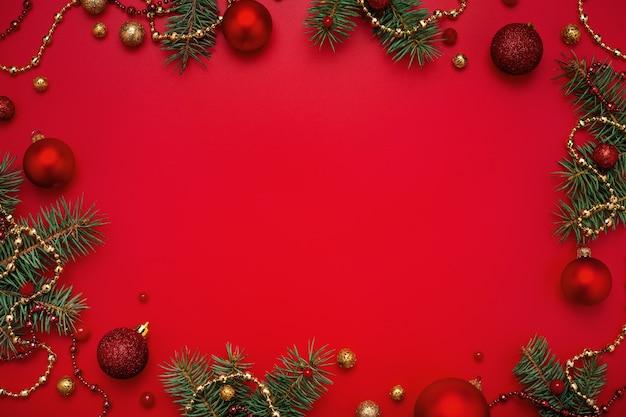 Regali di natale e abete con decorazioni in oro su sfondo rosso spazio copia.