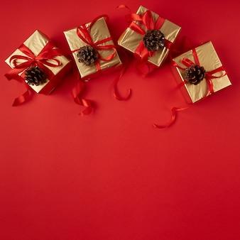 Regali di natale in carta oro con nastro rosso