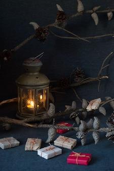 Regali di natale, sorbo, noci, vecchia lampada e ramo di pino con coni su superficie scura