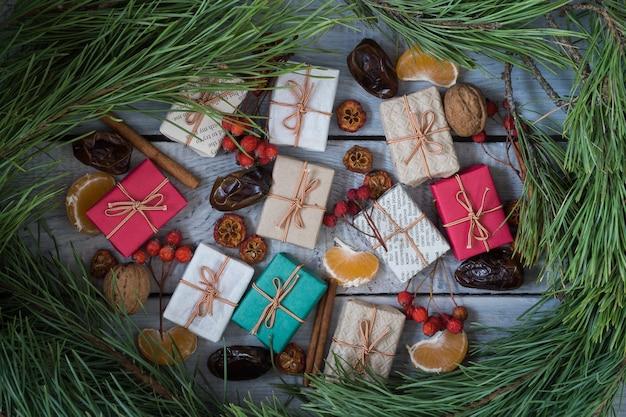 Regali di natale, sorbo, noci, ramo di pino, sparsi su tavole bianche dipinte ruvide