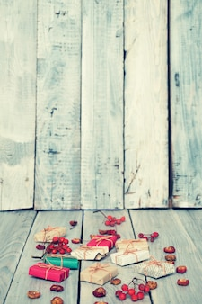 Regali di natale, sorbo, noci, sparsi su tavole bianche dipinte ruvide