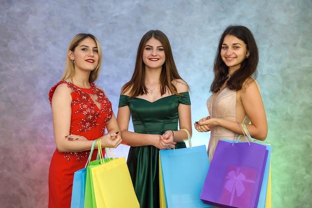 Regali di natale, tre giovani donne con borse presenti in posa in abito elegante