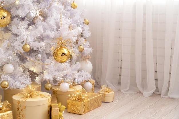 Regali di natale sotto un albero di natale bianco