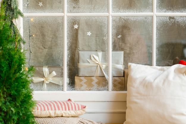 Regali di natale dietro una finestra della casa