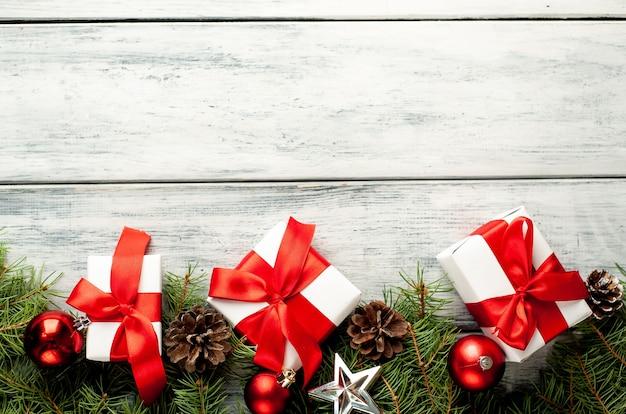 Regali di natale con nastro rosso, albero di natale e giocattoli di capodanno sulla tavola di legno