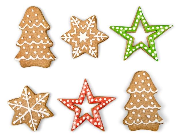 Biscotti allo zenzero e miele di natale su sfondo bianco isolato. stella, abete, a forma di fiocco di neve