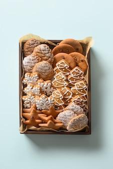 Biscotti di panpepato di natale in scatola come regalo fatto a mano. cartolina d'auguri verticale di natale.