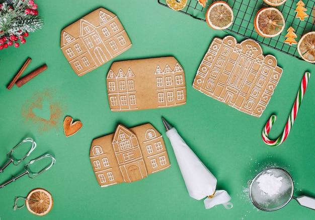 Biscotti di panpepato di natale case sulla superficie verde con sacchetto di glassa e fette di mandarino essiccate. vista dall'alto, piatto.