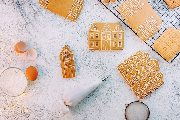 Biscotti di panpepato di natale case sulla superficie bianca con sacchetto di glassa e ingredienti. vista dall'alto, piatto.