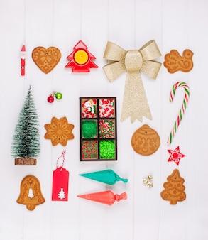 Biscotti di panpepato di natale, sacchetti di glassa, spolverata e decorazioni su superficie di legno bianca. vista dall'alto, piatto.