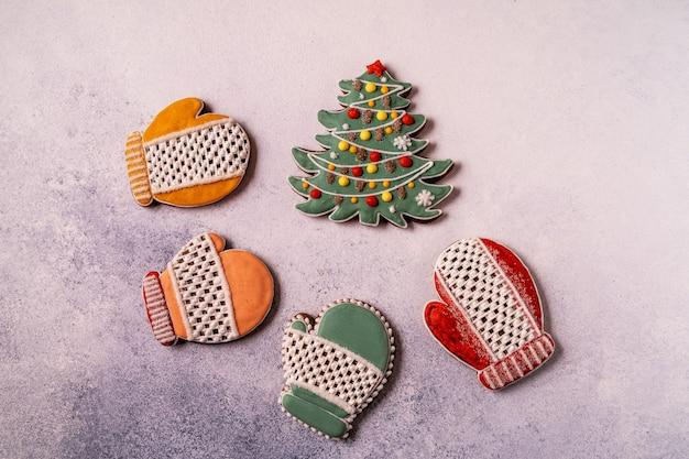 Pan di zenzero di natale su sfondo grigio cemento. avvicinamento. fiocco di neve, abete rosso, stella, slitta, coni, cono, stella, forma a campana.
