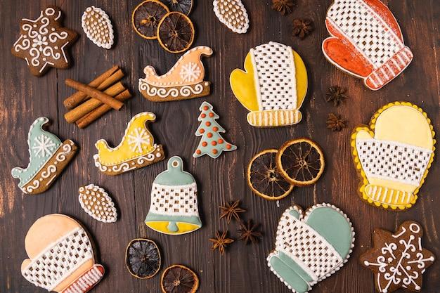 Pan di zenzero di natale su fondo di legno marrone. fiocco di neve, abete rosso, stella, cono, stella, forma a campana