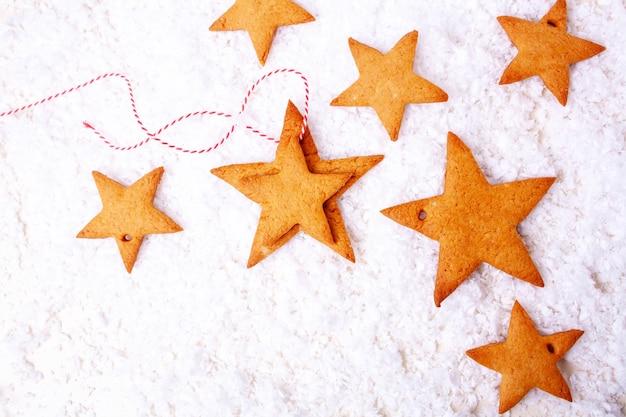 Pan di zenzero di natale a forma di stella su uno sfondo di neve