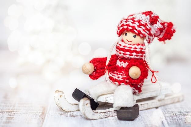 Giocattolo della bambola della ragazza di natale su una slitta per la decorazione