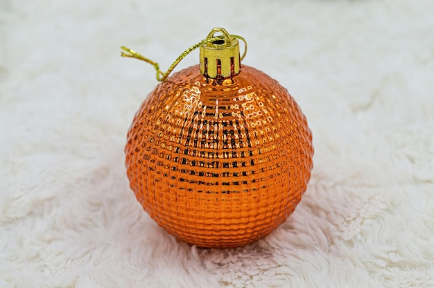 Palla di natale in vetro lucido arancione su sfondo di pelliccia bianca.