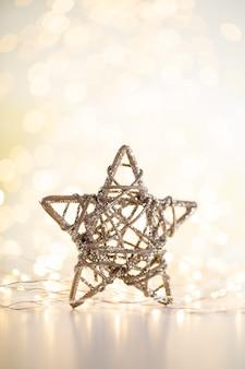 Fondo del bokeh dell'oro di natale con la stella decorativa