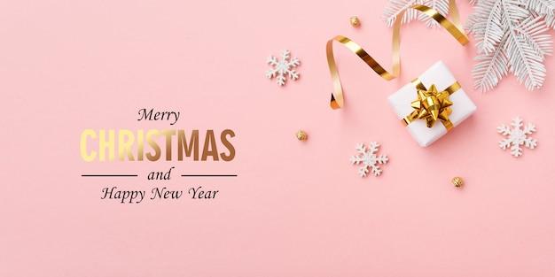 Decorazioni natalizie in oro su sfondo rosa pastello